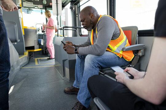 Construction worker using smart phone on public transit bus