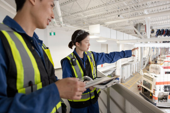 Workers talking on platform in maintenance facility