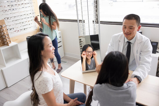 Optician helping mother and daughter try one eyeglasses