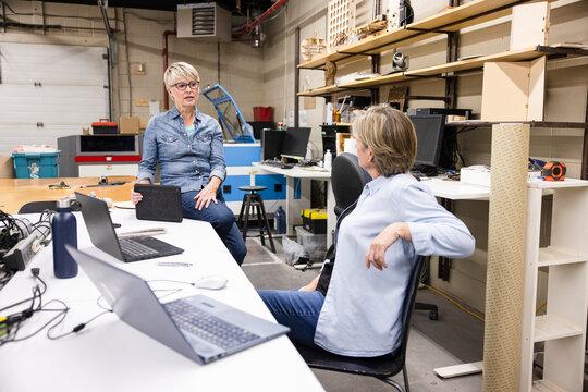 Senior female makers planning at laptops in workshop