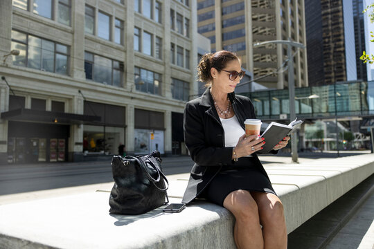 Businesswoman with coffee reading book in sunny city