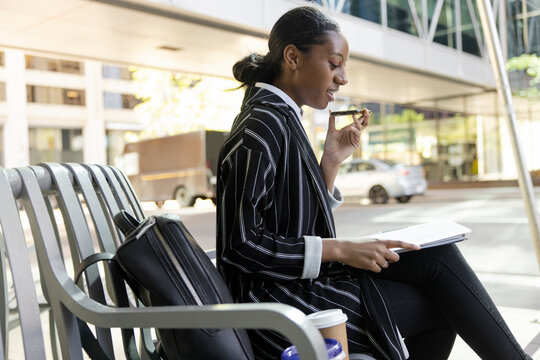 Young businesswoman talking on smart phone on city bench
