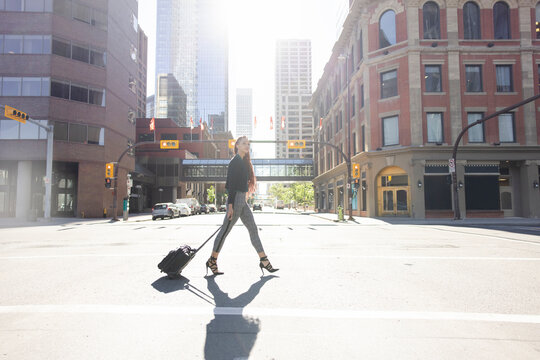 Businesswoman with rolling briefcase crossing sunny city street