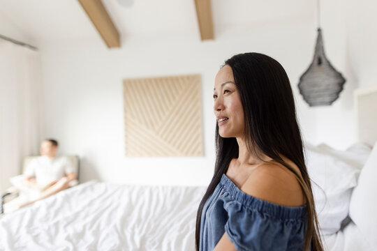 Beautiful smiling woman looking away in bedroom