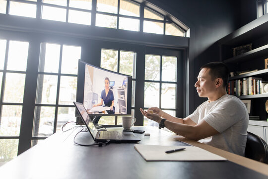 Man with medication video chatting with doctor on computer screen