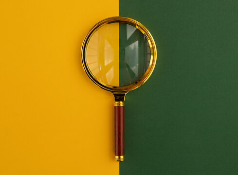 Magnifying lens over yellow and green paper.