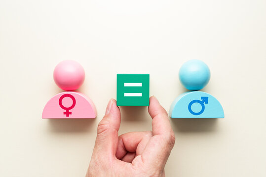 Gender equality. Hand putting equal sign block between female and male symbols.