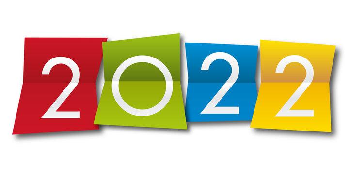 Carte de vœux 2022 avec l'année inscrite sur quatre papiers de couleurs différentes, pour présenter la nouvelle année.