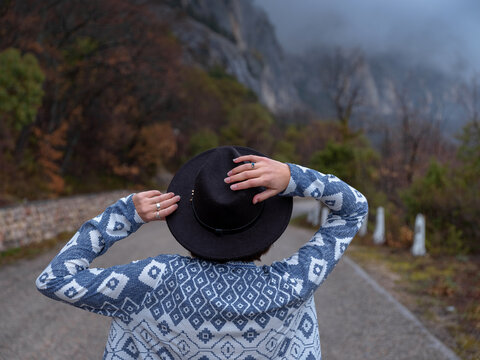 Back view of Stylish hipster woman in hat and poncho walking down a mountain road. The concept of travel and wanderlust. An amazing atmospheric moment