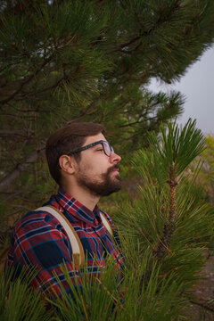 Male hipster Traveler with backpack in plaid shirt and jeans hiking in the mountains travel, trekking in autumn countryside. among the green pines