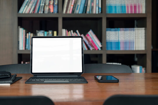 Blank screen laptop and gadget on wooden table in library room.