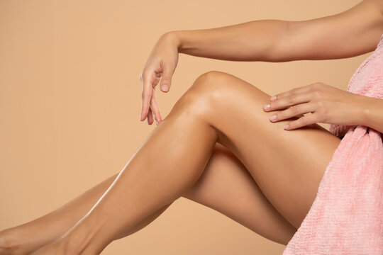Close-up on a woman touches her beautiful legs