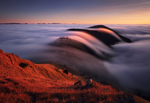 Mountain landscape above clouds at sunset in Slovakia with forest and sun