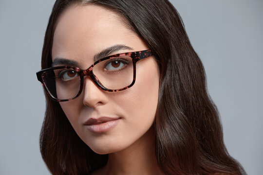 Confident young business woman 35-45 years old, brunette in stylish formal clothes and glasses, gray background, close-up. Business and career success concept.