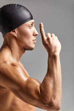 Young professional swimmer man indicates with fingers up showing a blank space.