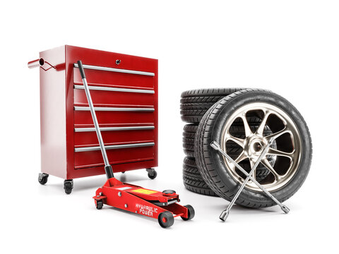 Set of tires, hydraulic car jack and workshop tool cabinet on white