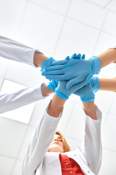 Hands in blue gloves covid, concept - creative team with hands on top of each other. Diverse team putting their hands together. One for all gesture in gloves. Covid-19 concept.