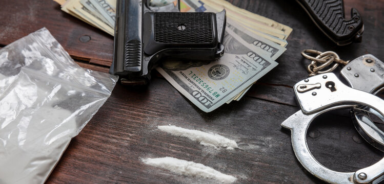 Drugs smuggling and trafficking, Handcuffs, pistol money and cocaine on wooden table background