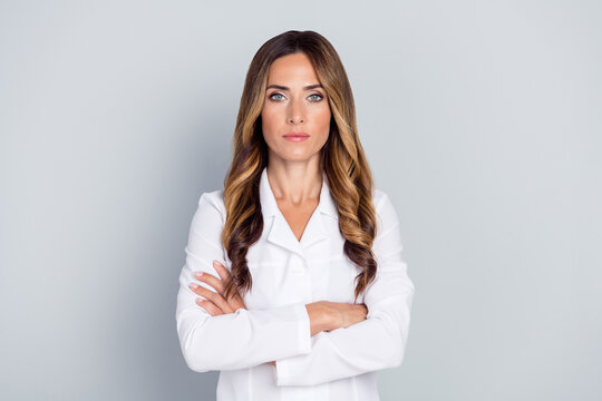 Photo of mature serious brown hairdo lady crossed arms wear white nurse coat isolated on grey background