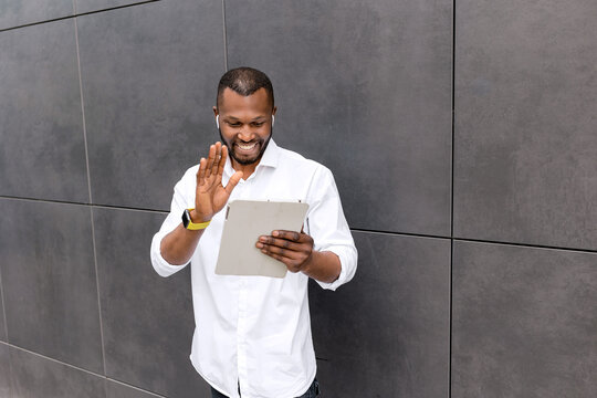 Joyful male employee or student using tablet, having video call, waving hello to coworkers or friends. Stylish businessman discuss project with colleagues at online conference, remotely work concept