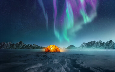 A tent pitched up in snow at night with the northern lights flickering in the sky above. Aurora Borealis and travelling. Photo composite.