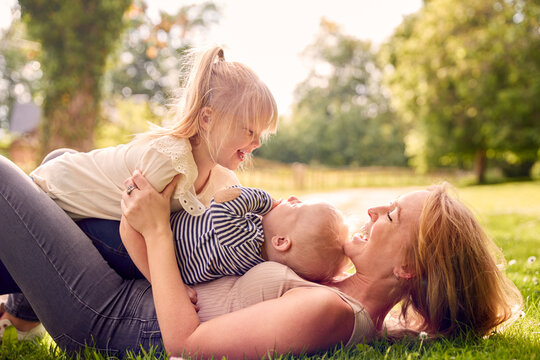 Mother And Children Having Fun Outdoors With Children Lying On Top Of Her On Grass