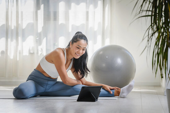 Young Asian woman exercising at home, attending an online yoga class