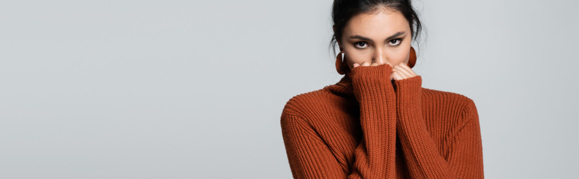 young woman in knitted sweater looking at camera while covering face isolated on grey, banner