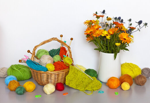 Bright autumn still life with orange, green and colorful balls of woolen yarn in wicker basket and vase with calendula flowers on the table. Needlework and knitting as hobby and leisure. DIY concept