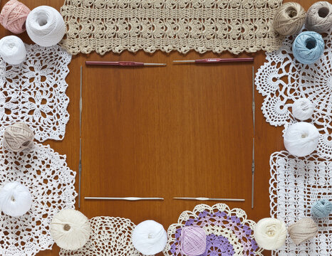 Top view of crochet accessories and different types of handmade lace napkins on a wooden table as a frame for text or an announcement. DIY concept. Flat lay, close up, copy space, mock up