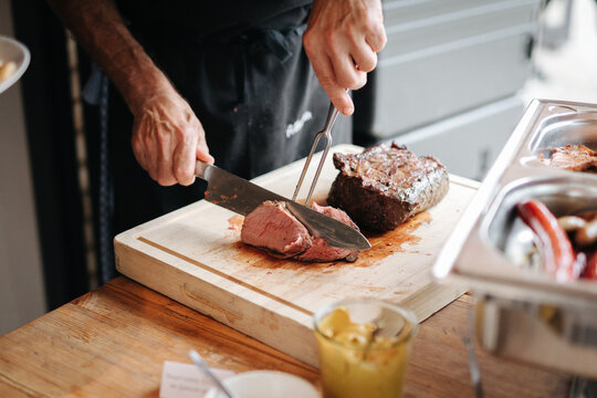 Cook cutting meat at a barbecue
