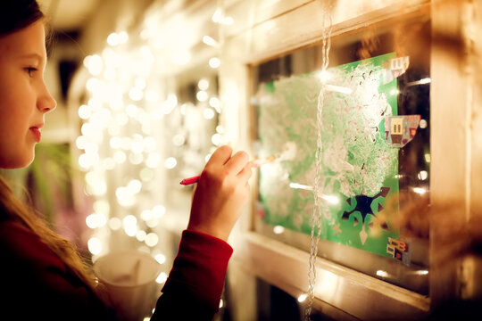 Drawing on the windows for Christmas. Baby girl decorates the house for christmas, paints the windows, dark style and festive lights on the background