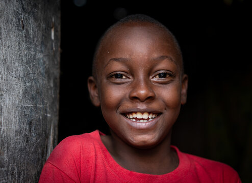 African black boy portrait standing near his poor house alone