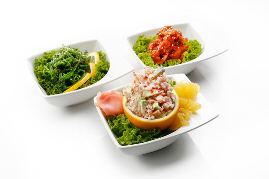 Composition of oriental appetizers in bowls, isolated on a white background. A pickled seagrass Japanese salad, a Korean kimchi and a shrimp, prawn salad. Packshot photo for sushi restaurant menu.
