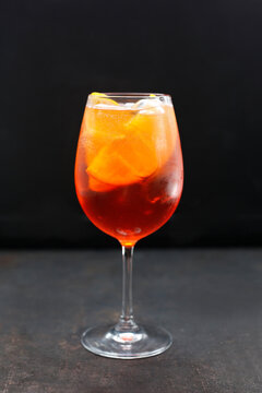 A red cocktail in a glass, side view. A colourful lemonade, red drink with ice cubes and orange wedges, on a black stony background, on a bar.