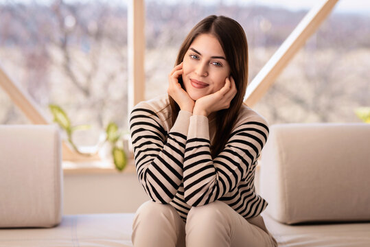 Smiling young woman wearing casual clothes while relaxing on the sofa at home
