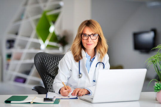 Female doctor using mobile phone and laptop while working at doctor's office