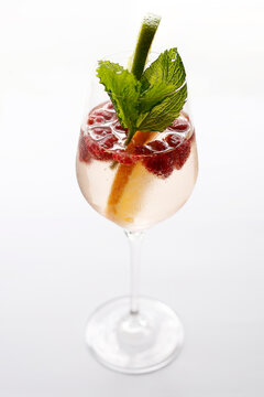 A drink, cocktail in a glass, selective focus, isolated on white. A lemonade with fresh raspberry fruits, garnished with fresh mint leaves.