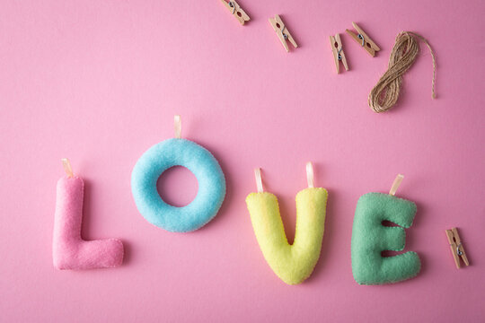 Love concept with letters on pink surface, greeting card