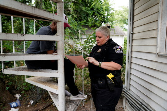 Oklahoma County Deputy Sheriff Melody Norton explains an eviction court summons to a man who said he suffers from mental disabilities and depends on Section 8 to pay his rent in Oklahoma City