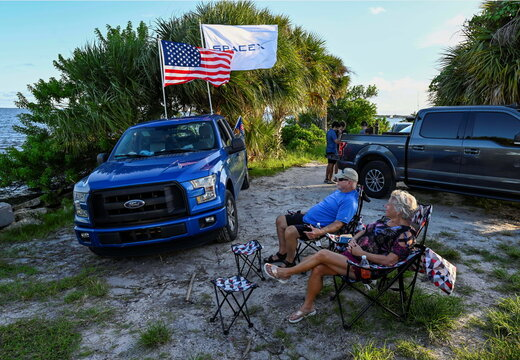 The Thurmans wait for the launch of the SpaceX Falcon 9 rocket as they sit along the Indian River Lagoon
