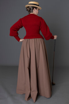 An 1890s woman wearing a golfing ensemble including a red jumper