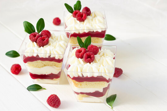 Dessert with raspberry , delicious  dessert with fresh berries., portion dessert in a clear plastic cups. White wooden board, healthy eating , healthy dessert, red berries cake