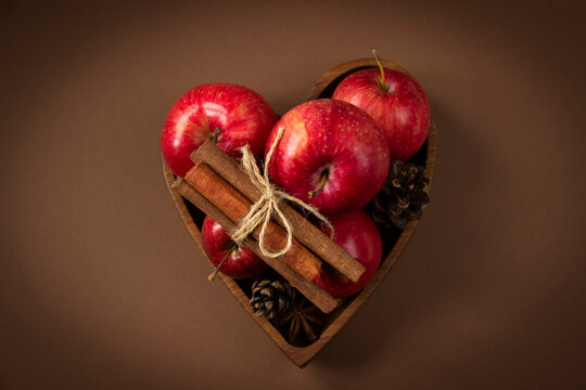 Red ripe apples, cinnamons sticks, pine cones in wooden plate heart shape on brown background. Autumn harvest, autumn template from Thanksgiving. Apples and cinnamon heart