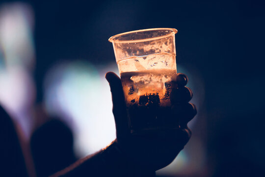 Person holding cold beer plastic cup on a music festival.