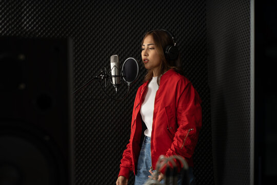Asian singer woman in a recording studio using a studio microphone with passion in music recording studio