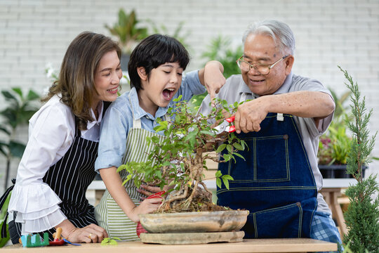 Happy family gardening together in the garden, grandfather grandson and woman taking care of nature