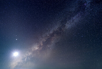 Fototapeta the milky way with bright moon light in stary night obraz