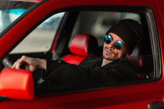 cool young male driver wearing sunglasses is driving a red car. Guy travels behind the wheel