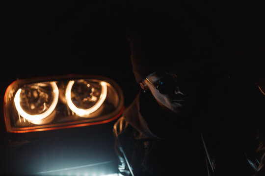 Stylish man in a black leather jacket with fashionable sunglasses sits near a headlight in the dark